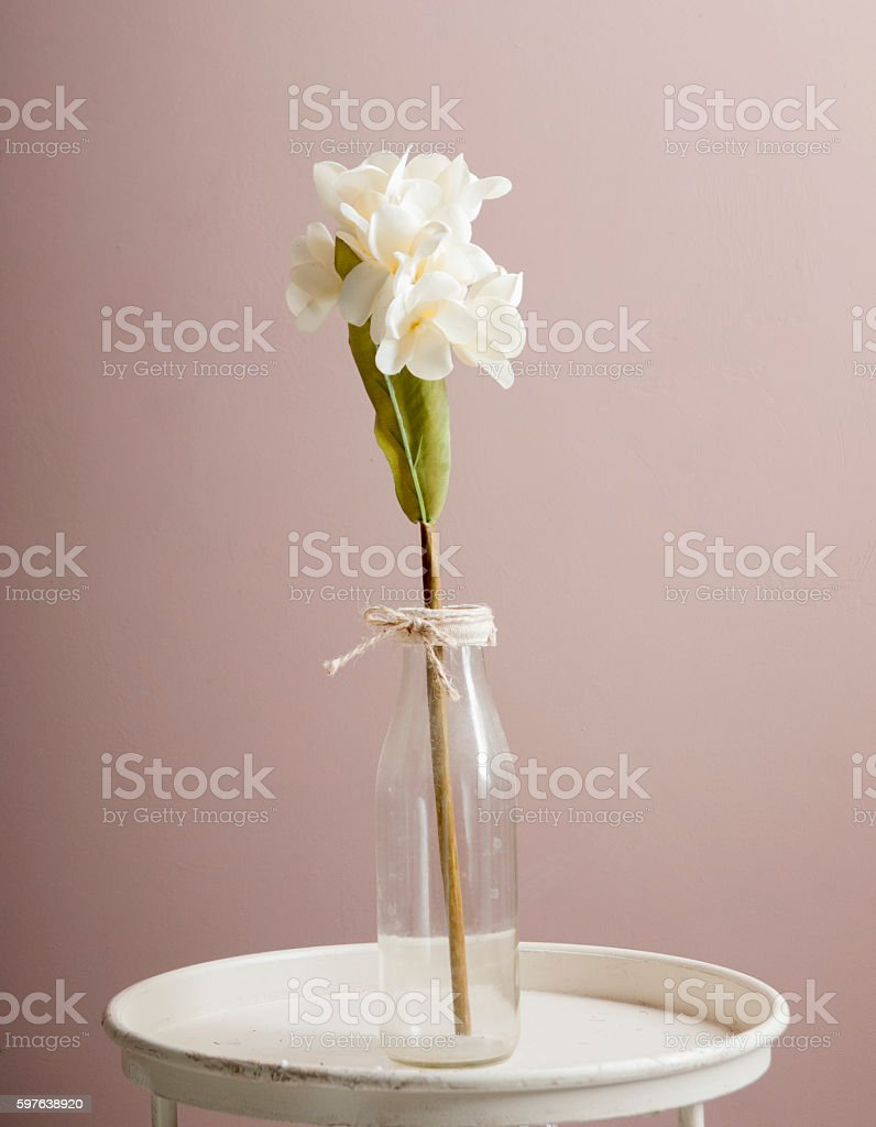 Artificial white orchid in a glass bottle. stock photo