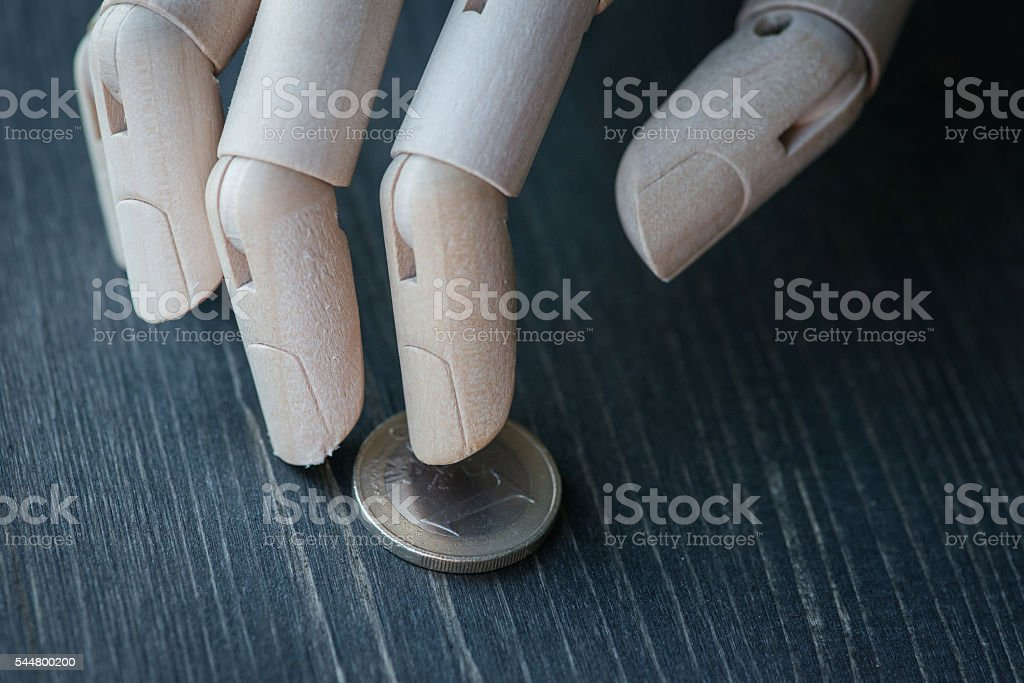 Artificial wooden hand holding the money, on a wooden table stock photo