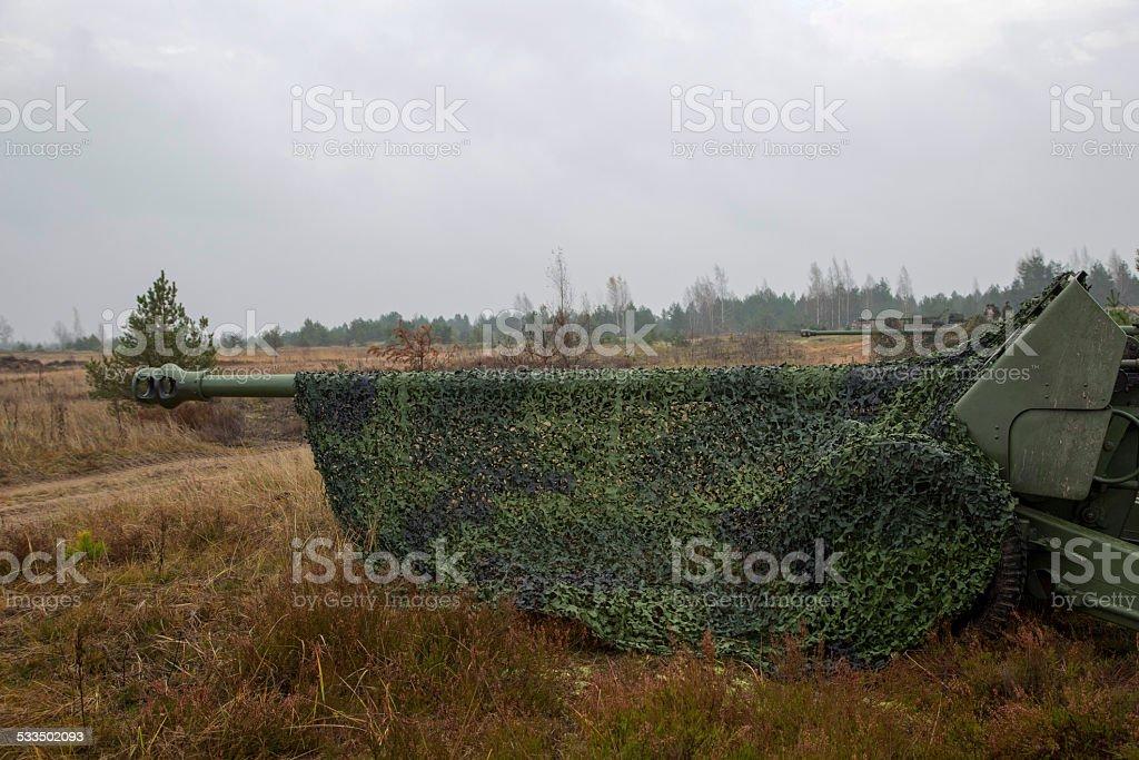artillery gun under camouflage net stock photo