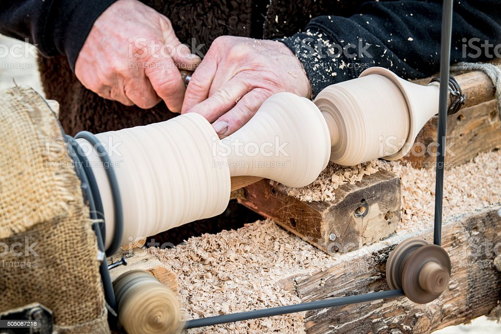 Artisan carves a piece of wood using a manual lathe. stock photo