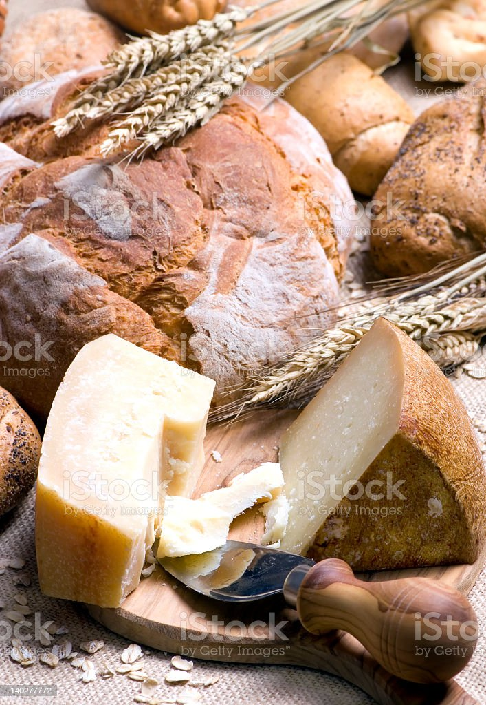 Artisan cheese and breads on a wooden cutting board royalty-free stock photo