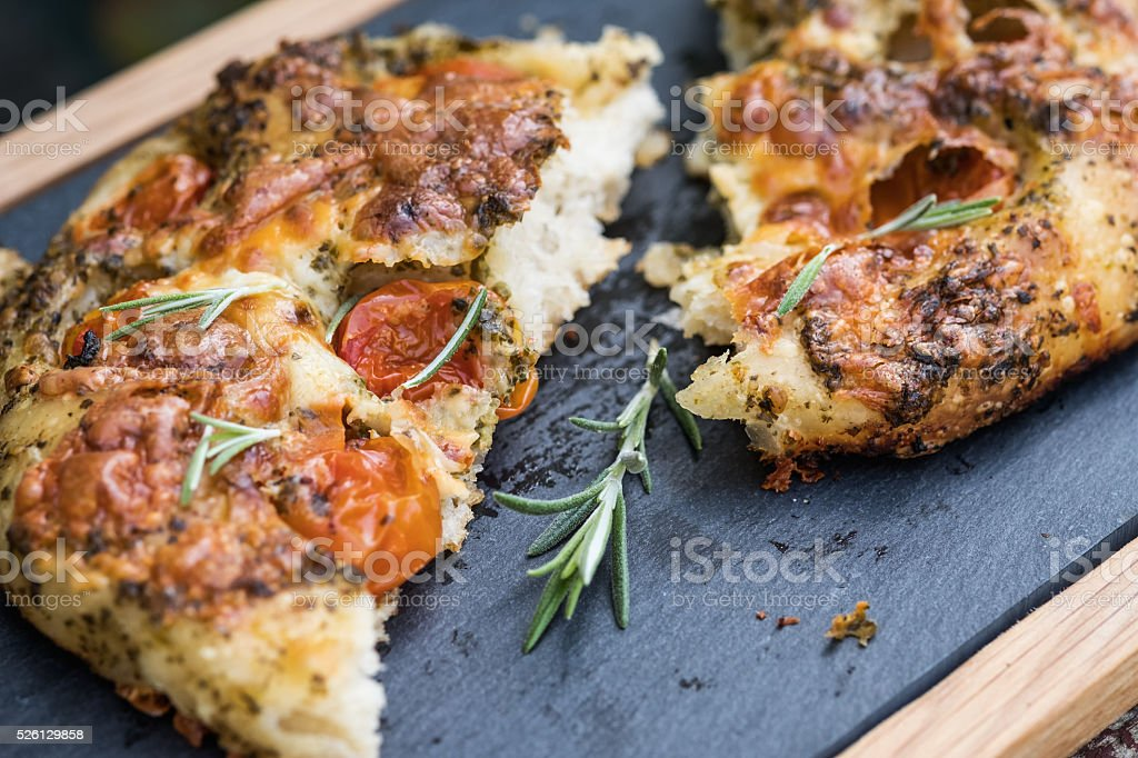 Artisan Focaccia Bread Pizza with Cherry Tomatoes, Pesto, Rosemary stock photo