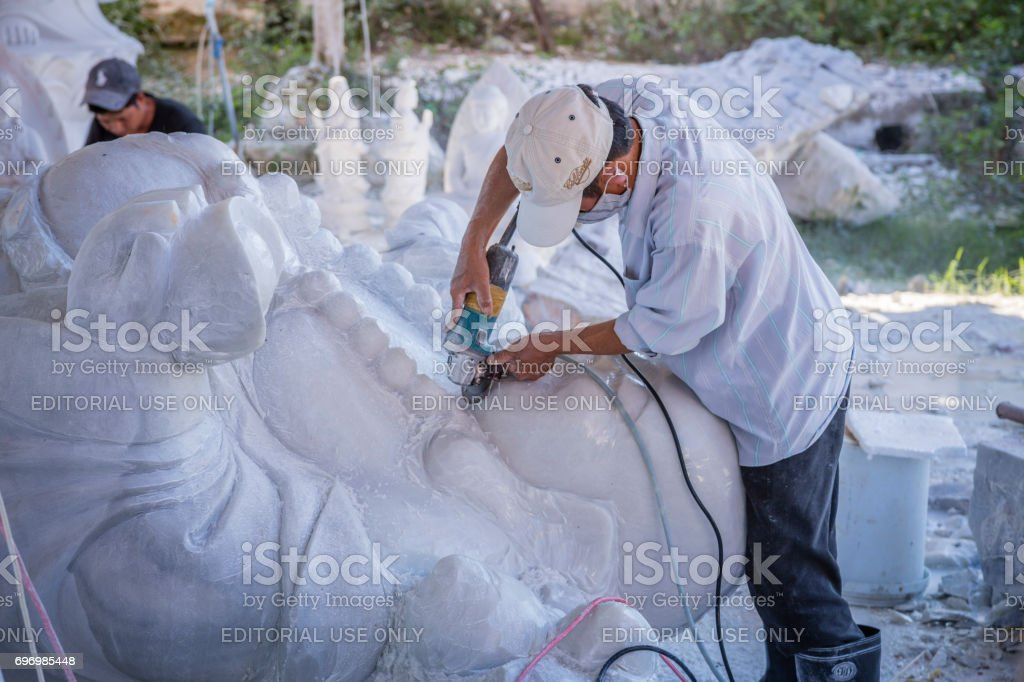 Artisan in full work of creation of a statue of marble Buddha stock photo