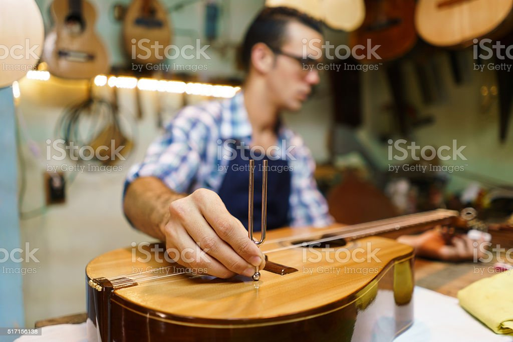 Artisan Lutemaker Tuning Handmade Classic Guitar With Diapason stock photo