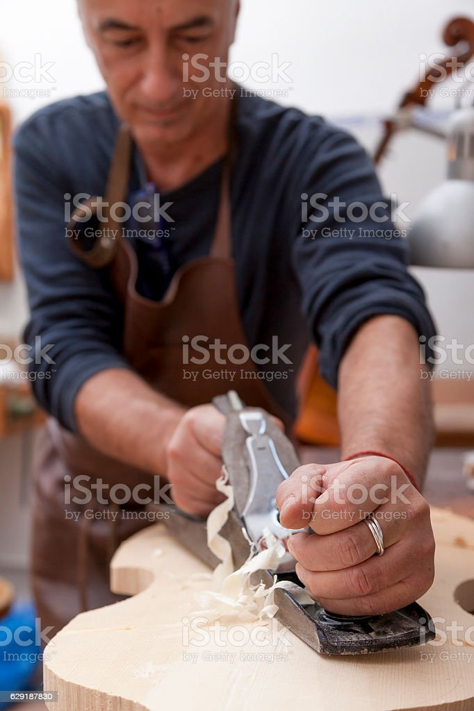 artisan lutemaker working a violin in his workshop stock photo