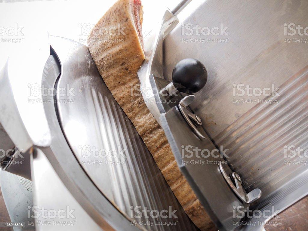 Artisan smoked bacon in a slicer stock photo