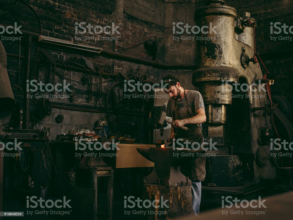 Artisan working iron in blacksmith's workshop stock photo