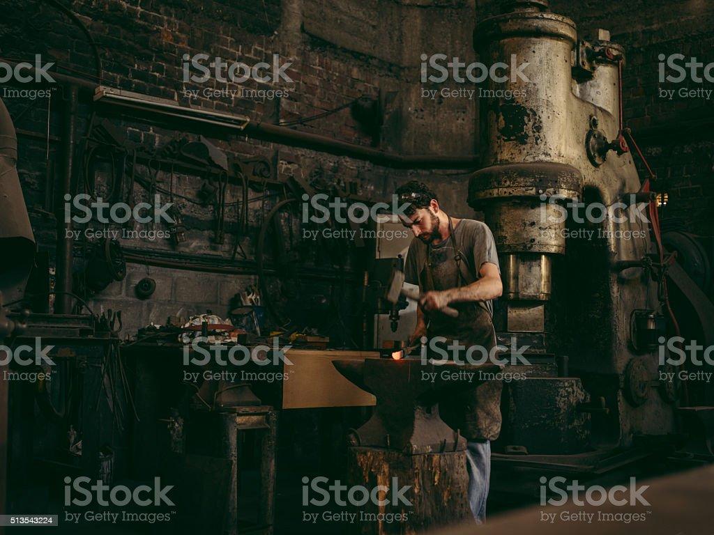 Artisan working iron in blacksmith's workshop stock photo
