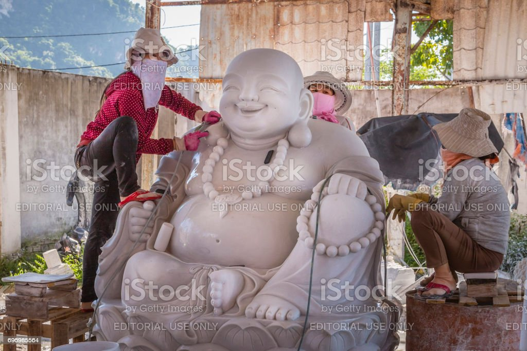 Artisans in full work of creation of a statue of marble Buddha stock photo