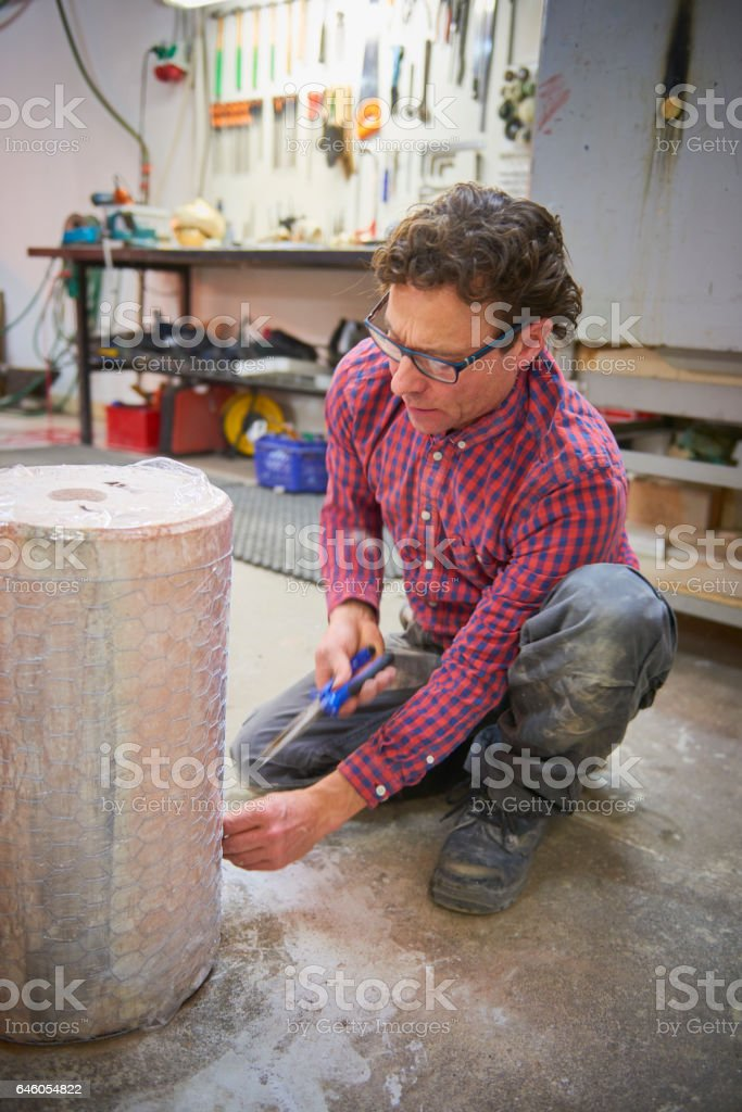 Artist and assistant handling mold for a sculpture stock photo