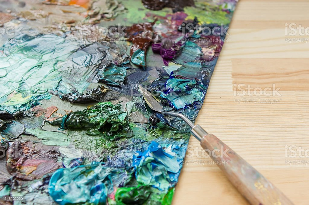 artist brushes, palette knife and palette with paints impression stock photo