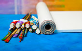 Artist canvas in roll, canvas stretcher and paintbrushes .