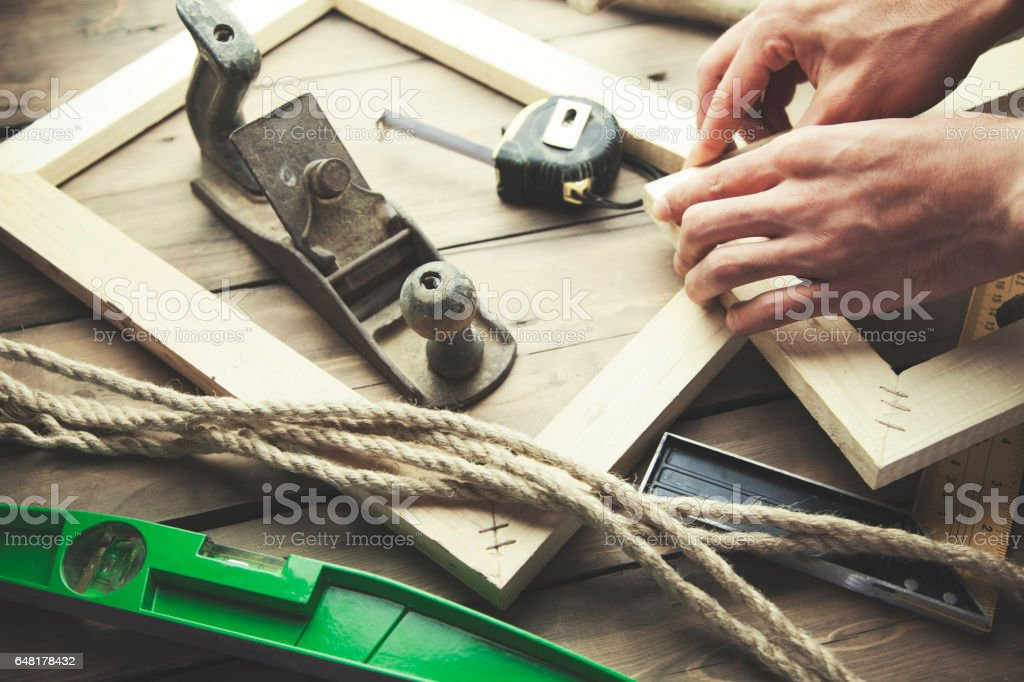 Artist canvas on man hand , canvas stretcher and staple gun on table stock photo