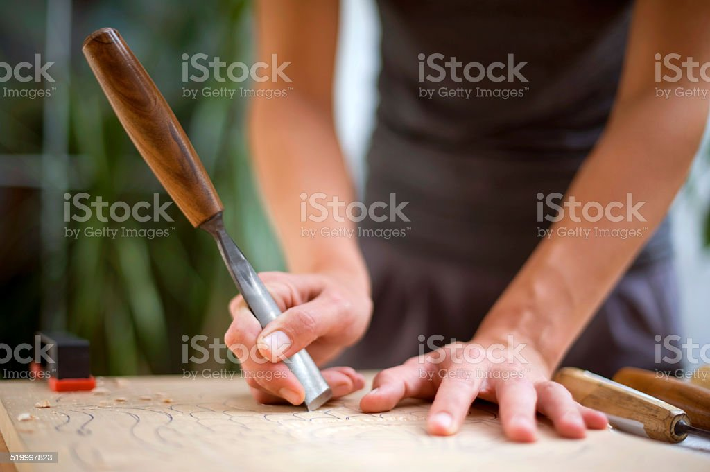 Artist carves a wooden plate with a chisel stock photo