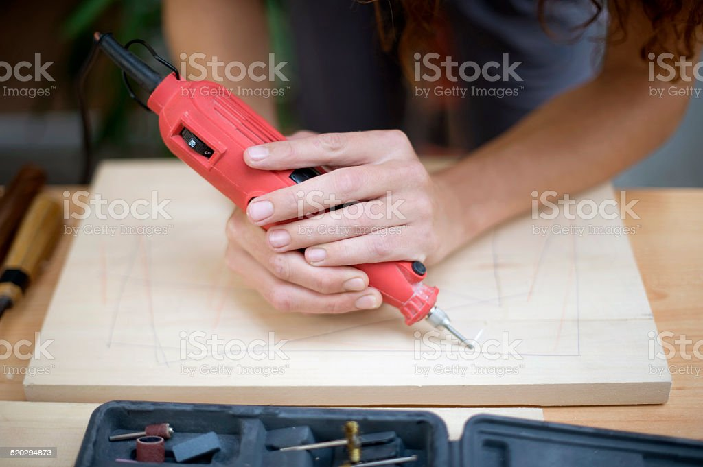 Artist carving wood with electric tool stock photo