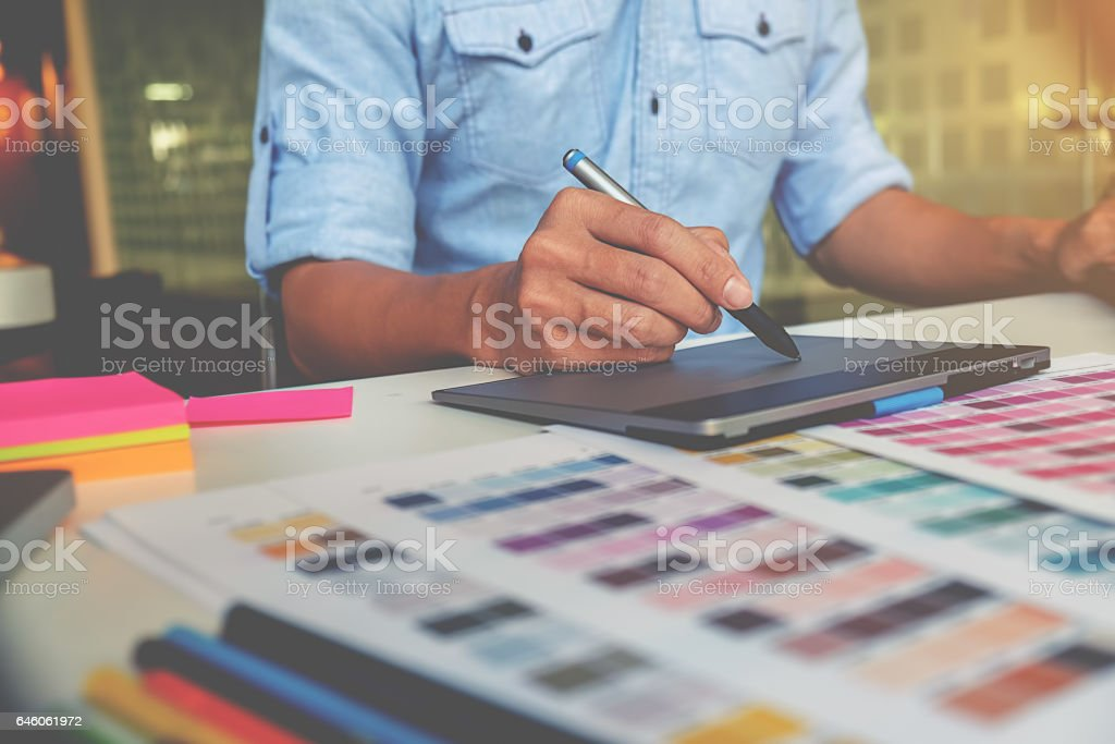 Artist drawing on graphic tablet in office stock photo
