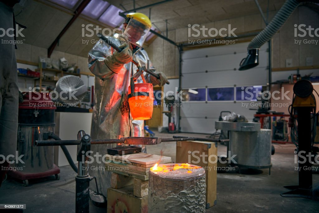 Artist fills mold with molten bronze stock photo