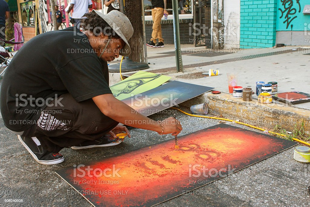 Artist Flicks Yellow Paint Onto Painting At Arts Festival stock photo