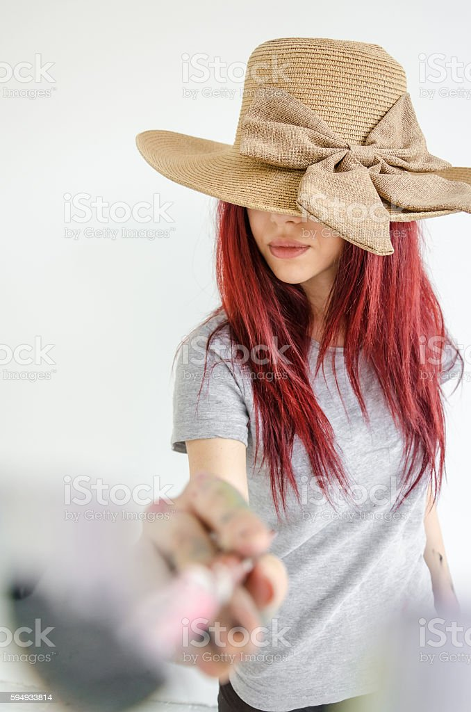 Artist girl painting a lens with brush stock photo