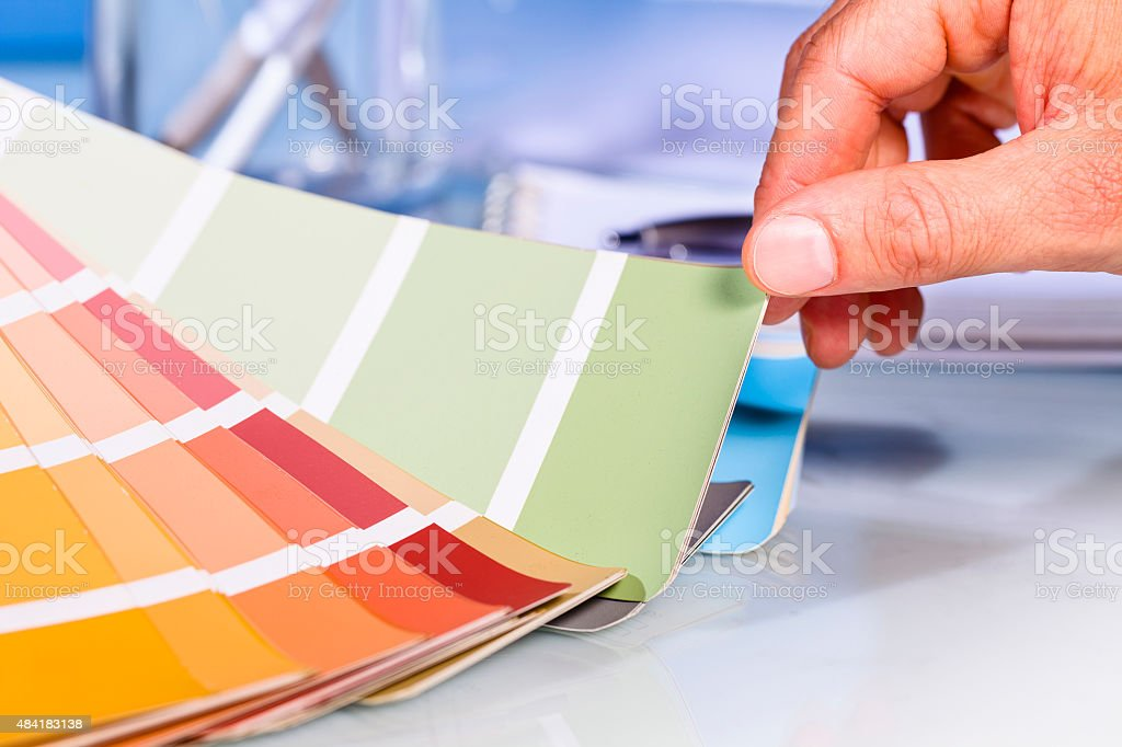 Artist hand browsing color samples in palette stock photo