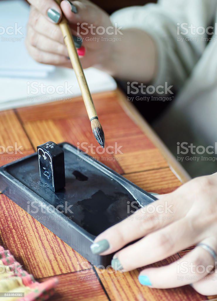 artist hand holding Fude brush for Sumi-e painting over suzuri stock photo