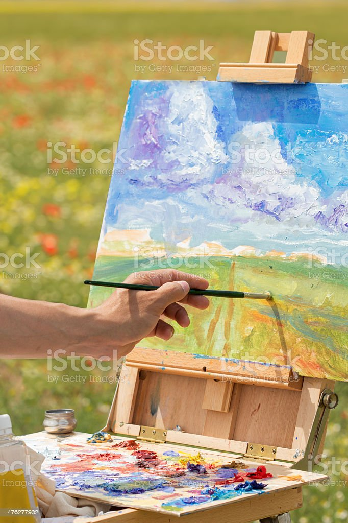 artist hand paints with brush on nature stock photo