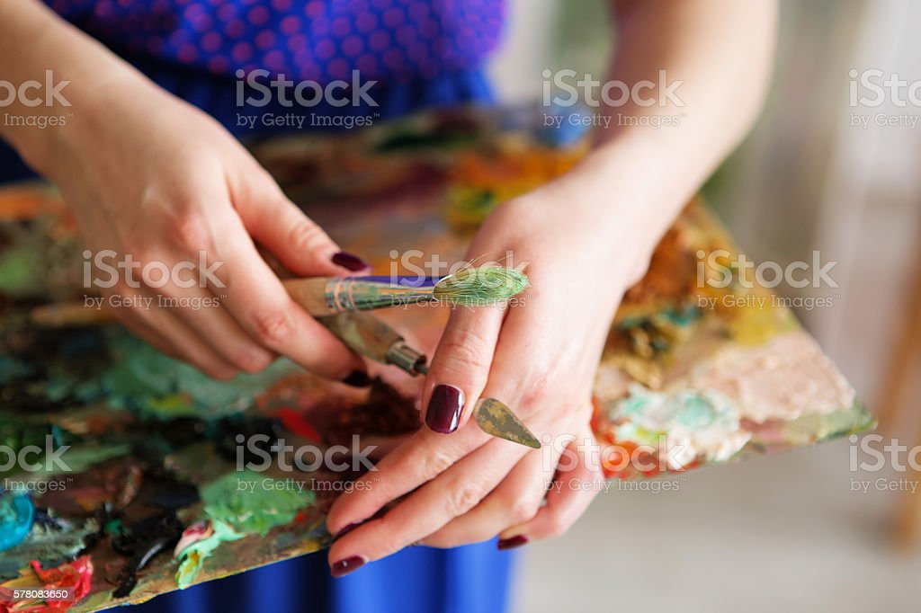 artist holding a palette with oil paints, brush and palette stock photo