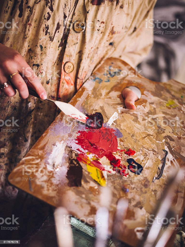 Artist holding palette and mixing colourful paint with palette k stock photo