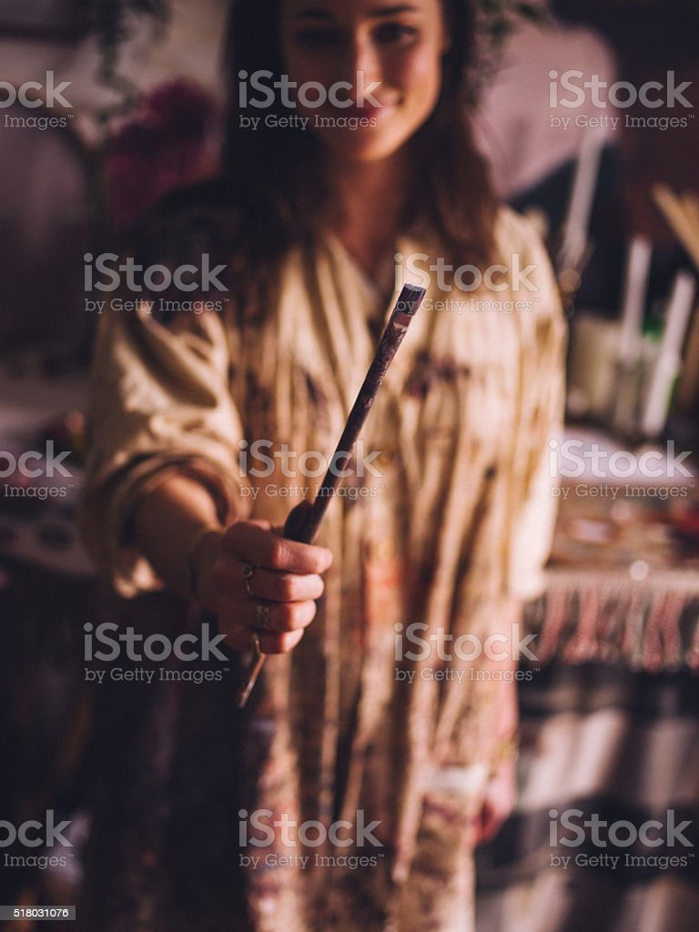 Artist in a dirty smock holding out a paintbrush stock photo