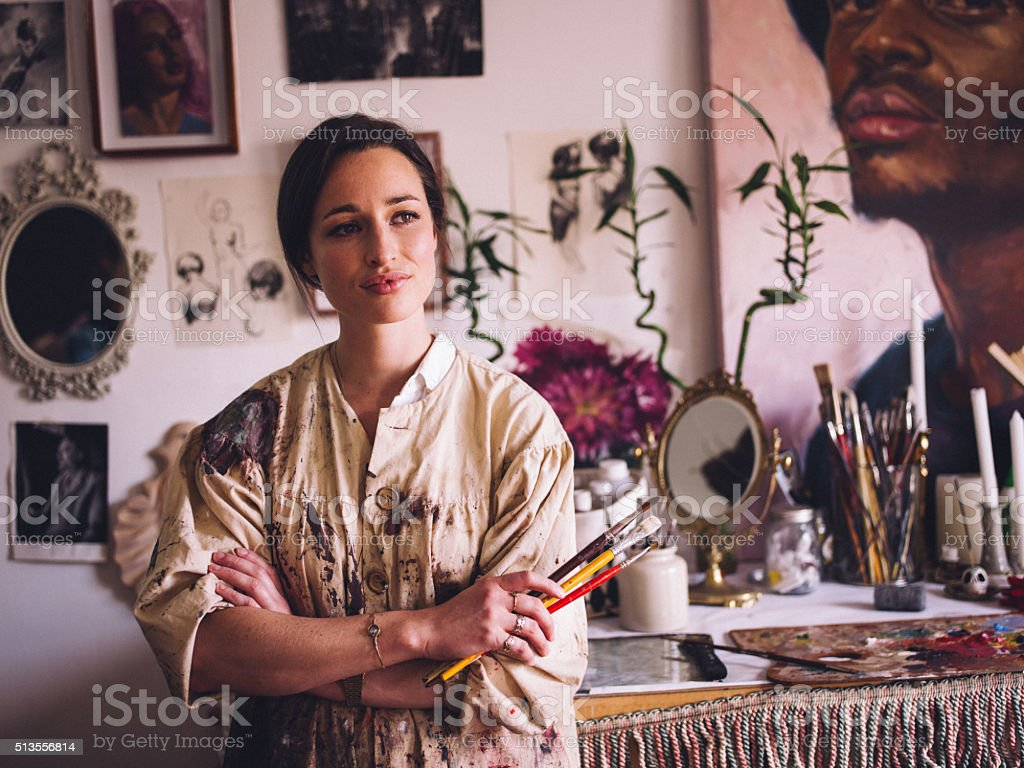 Artist in her studio wearing paint covered smock with paintbrush stock photo