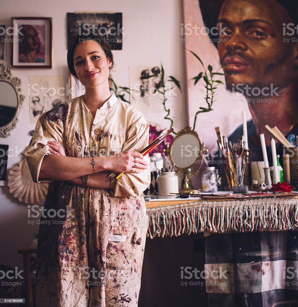 Artist in smock standing with paintbrushes at her work table stock photo