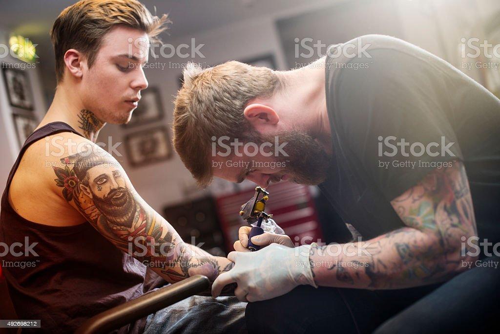 Artist making tattoo on man's hand stock photo