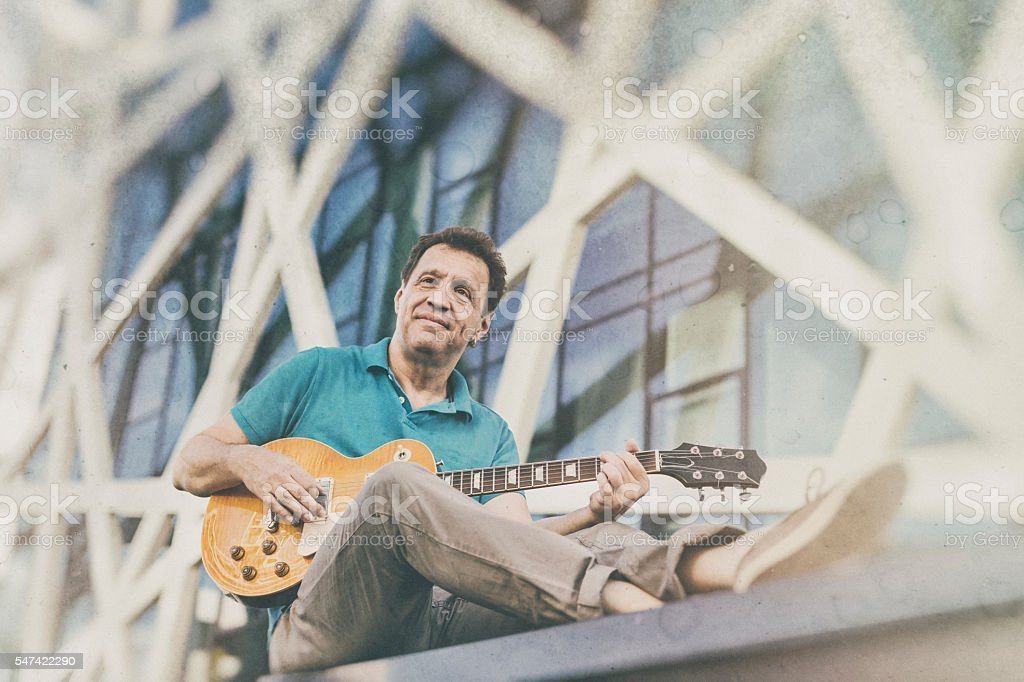 Artist musician playing the guitar outdoors stock photo