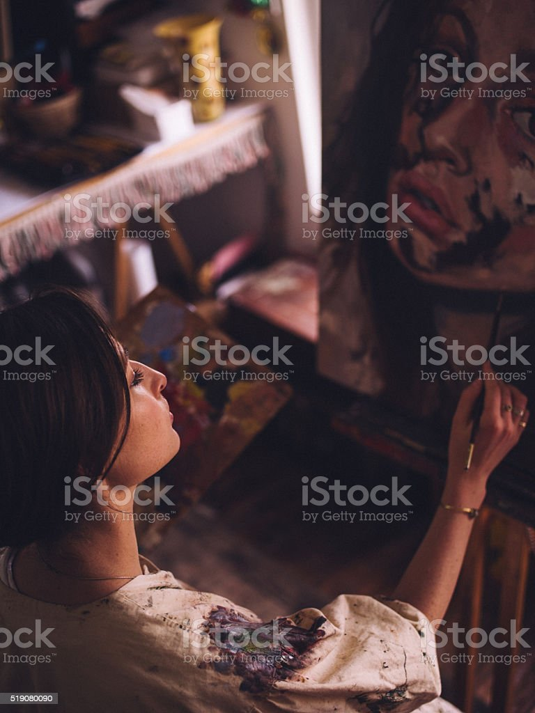 Artist painting a portrait with oil paints on a canvas stock photo