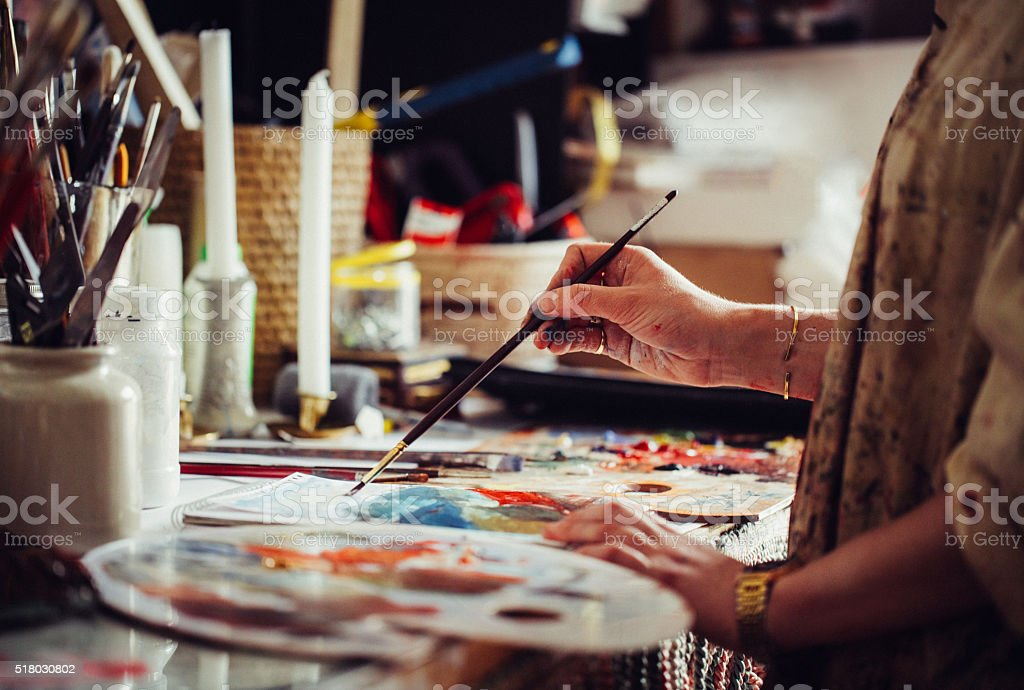 Artist painting at a table with a colourful palette stock photo