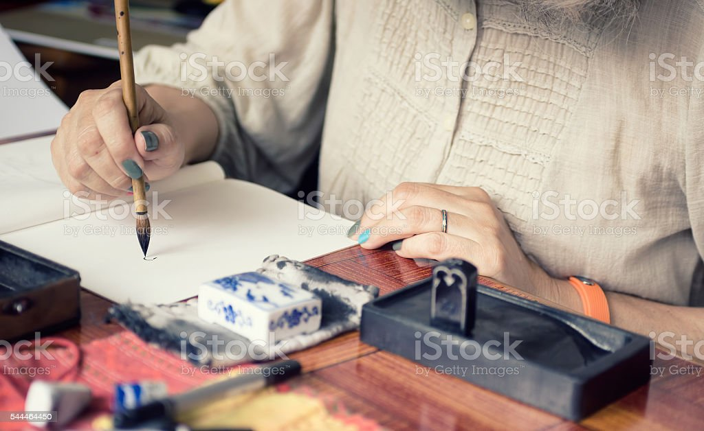 Artist painting in a traditional Japanese technique Sumi-e stock photo