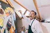 Artist painting in his workshop
