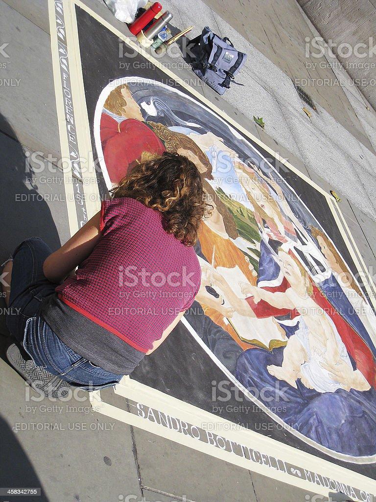 Artist painting on a pavement/sidewalk. stock photo