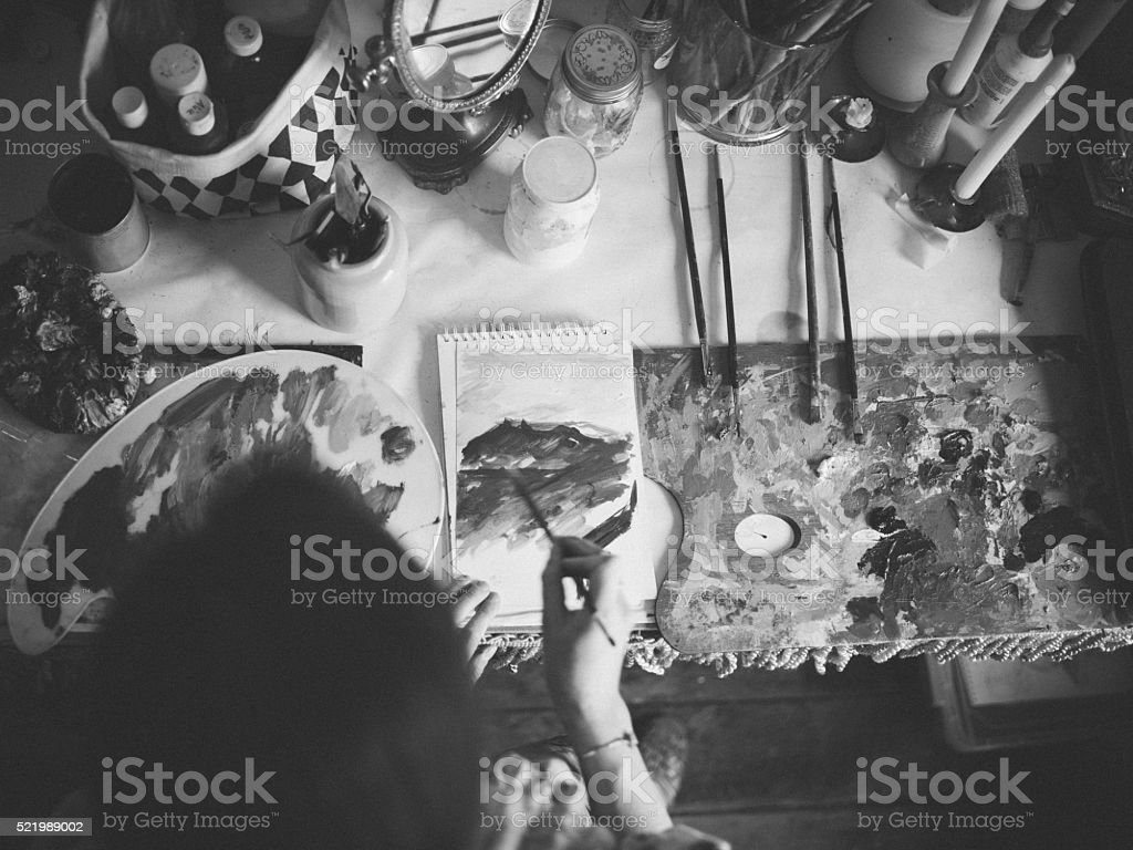 Artist painting on paper on a messy studio table stock photo