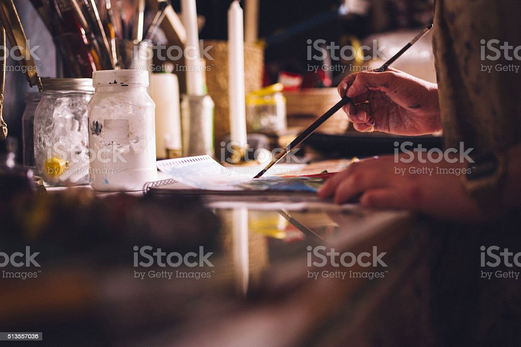 Artist painting on paper with a fine paintbrush stock photo