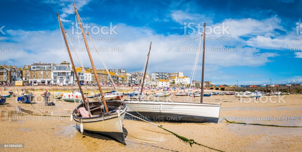 Artist painting wooden boats St Ives harbour beach panorama Cornwall stock photo