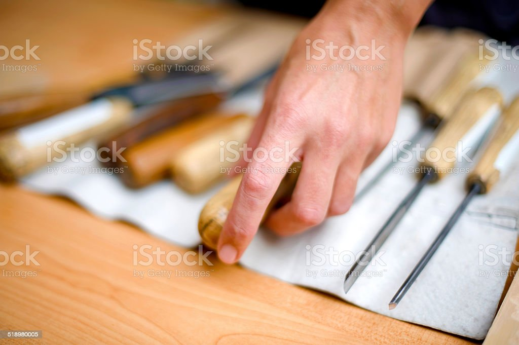 Artist picking cheesel for wood carving stock photo
