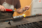 artist sculptor works on steel tube with brazing tools