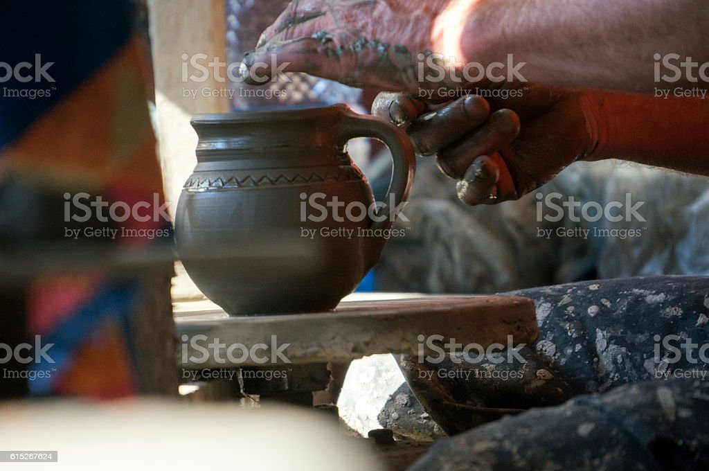 Artist shaping clay on the pottery wheel. stock photo