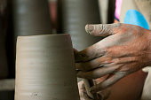 Artist shaping clay on the pottery wheel.