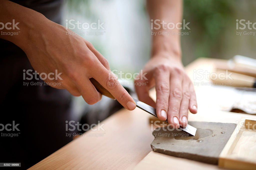 Artist sharp chisel with stone for sharpening stock photo