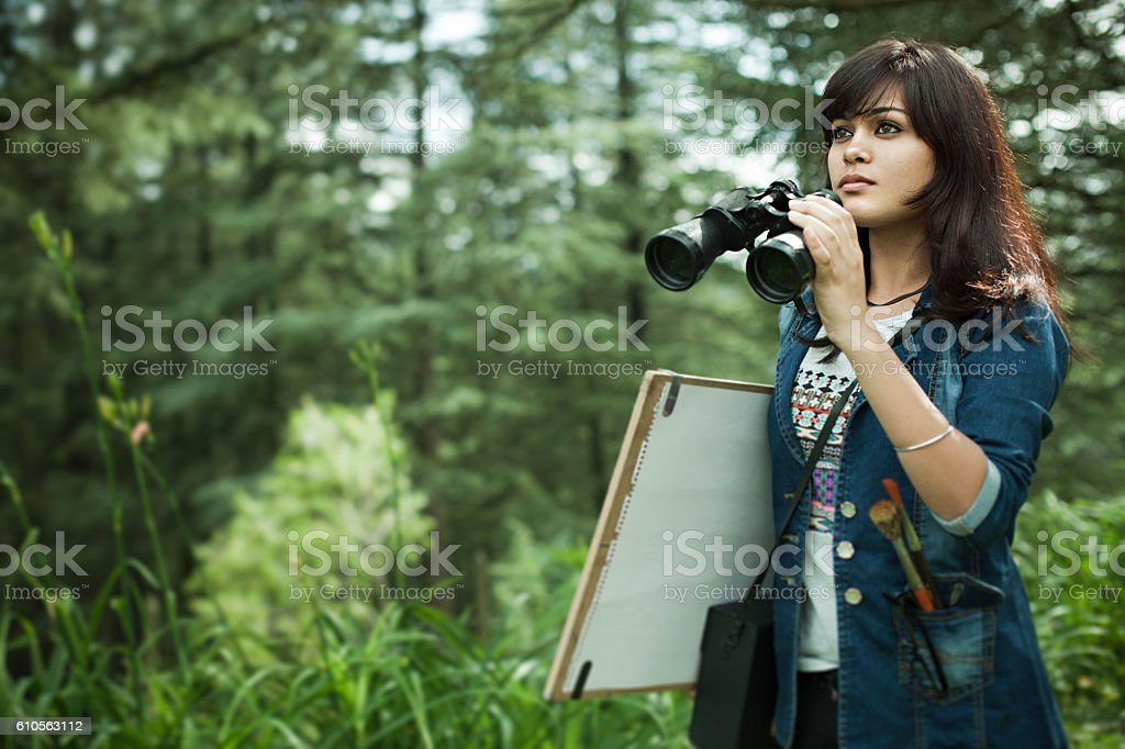 Artist with binocular, drawing board and art equipments searching subject. stock photo
