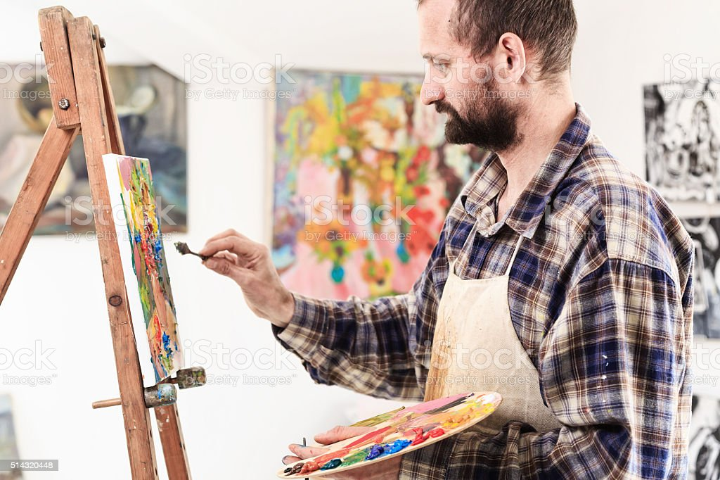Artist with paint palette in his workshop stock photo