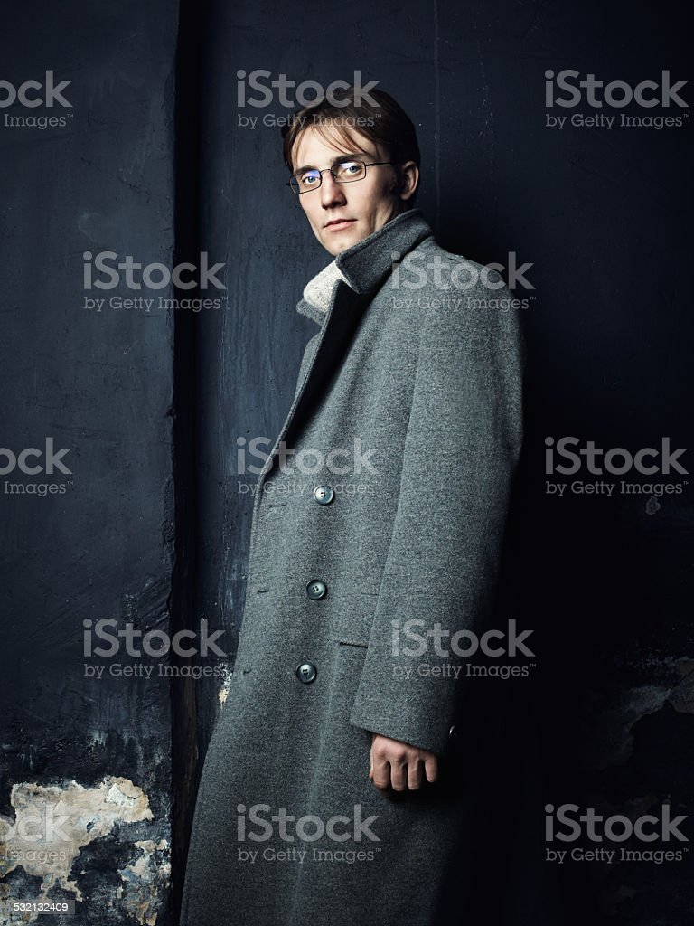 Artistic dark portrait of young man in gray coat stock photo
