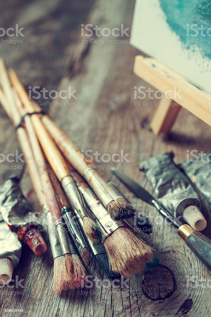 Artistic paintbrushes, tubes of paint, palette knife and easel. stock photo